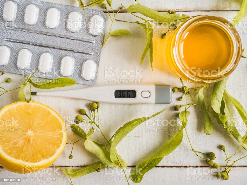 Electric thermometer, pills, fresh yellow lemon, jar of honey, linden...