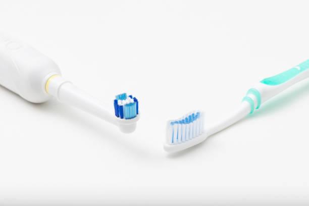 Electric toothbrush versus regular toothbrush stock photo