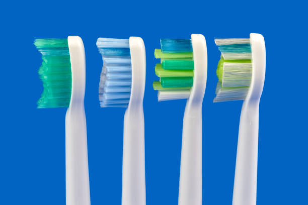 Electric toothbrushes at blue background stock photo