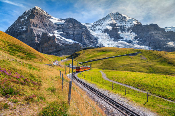 Electric tourist train and high snowy mountains with glaciers, Switzerland Famous electric red tourist train coming down from the Jungfraujoch station(top of Europe) in Kleine Scheidegg. Eiger North face in background, Grindelwald, Bernese Oberland, Switzerland, Europe swiss alps stock pictures, royalty-free photos & images