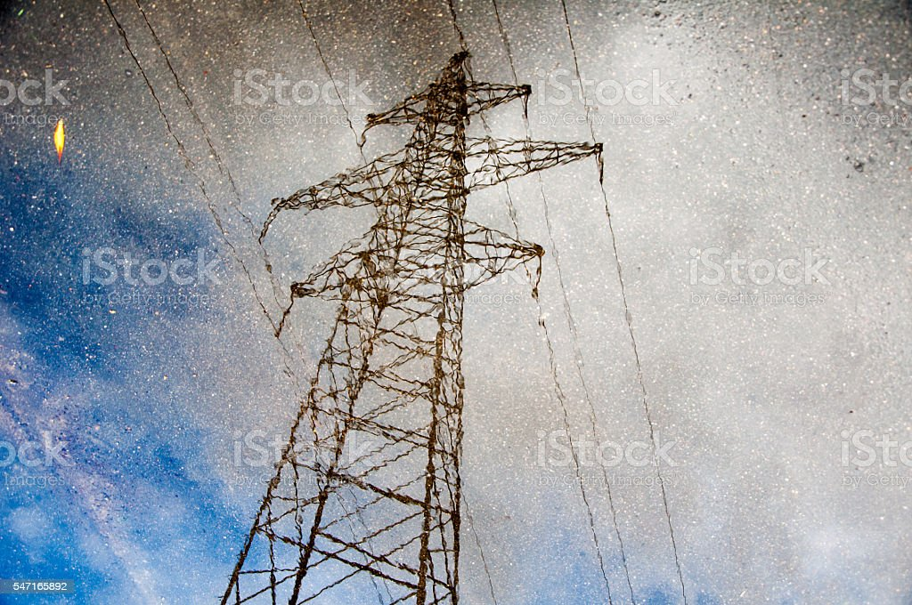 electric tower reflection on a water puddle stock photo