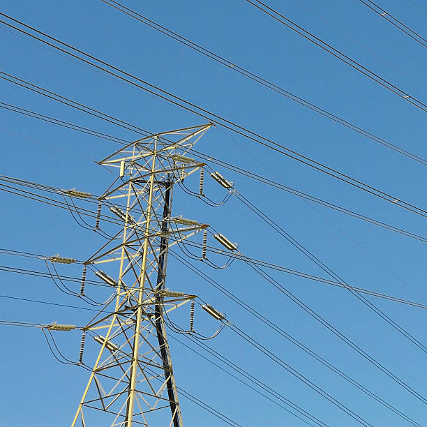 Electric transmission power lines isolated against a blue sky. stock photo