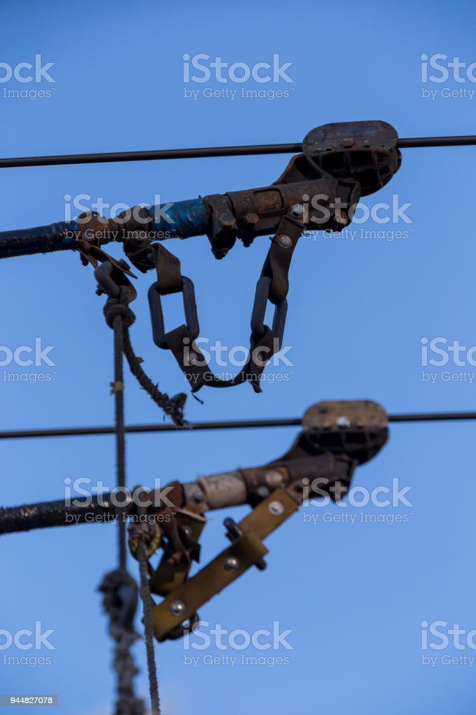 Electric trolleybus collectors close-up against the April blue spring sky. Power line wires network. Public transport. stock photo