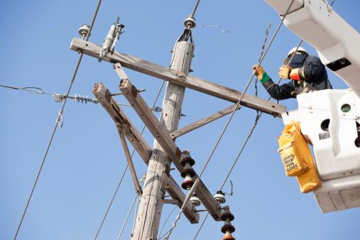 Electric Utility Lineman Repairing Damaged Pole