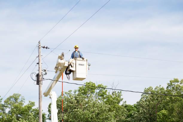 electric utility lineman arbeitet - waldhandwerk stock-fotos und bilder