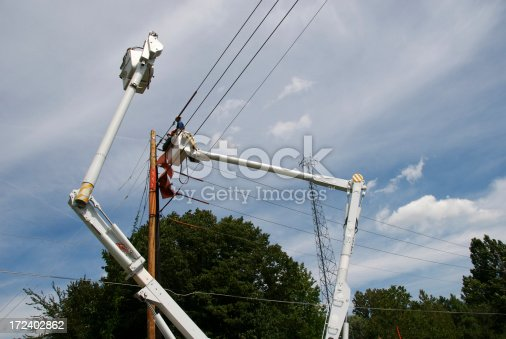 Installing new power lines from bucket trucks.