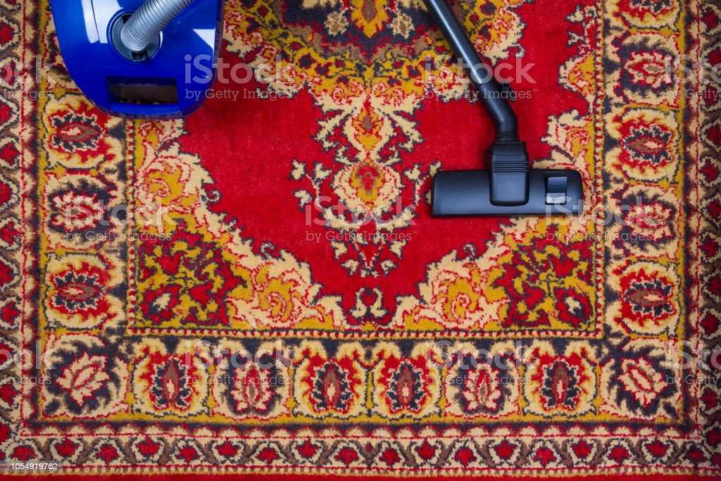 electric vacuum cleaner on the background of an old carpet, top view...