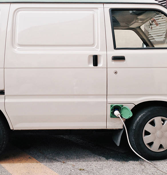 Electric van plugged in to recharge stock photo