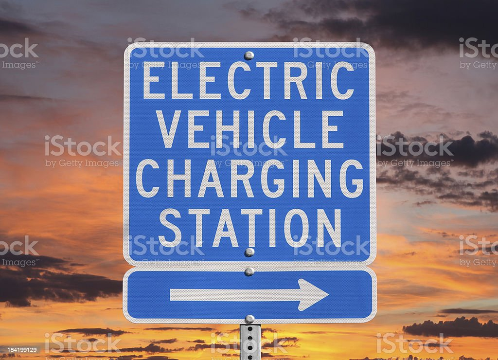 Electric Vehicle Charging Station Sign with Sunset Sky stock photo