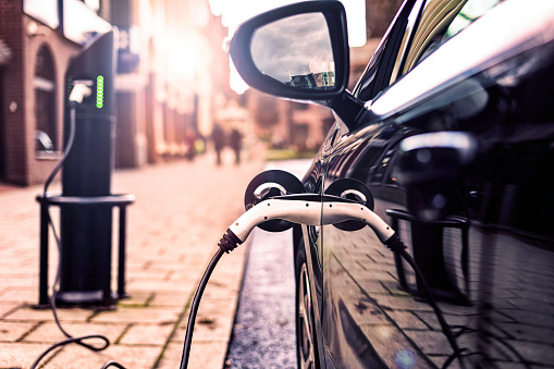 Electric Vehicle In Park Street Charging Station Stock Photo - Download Image Now