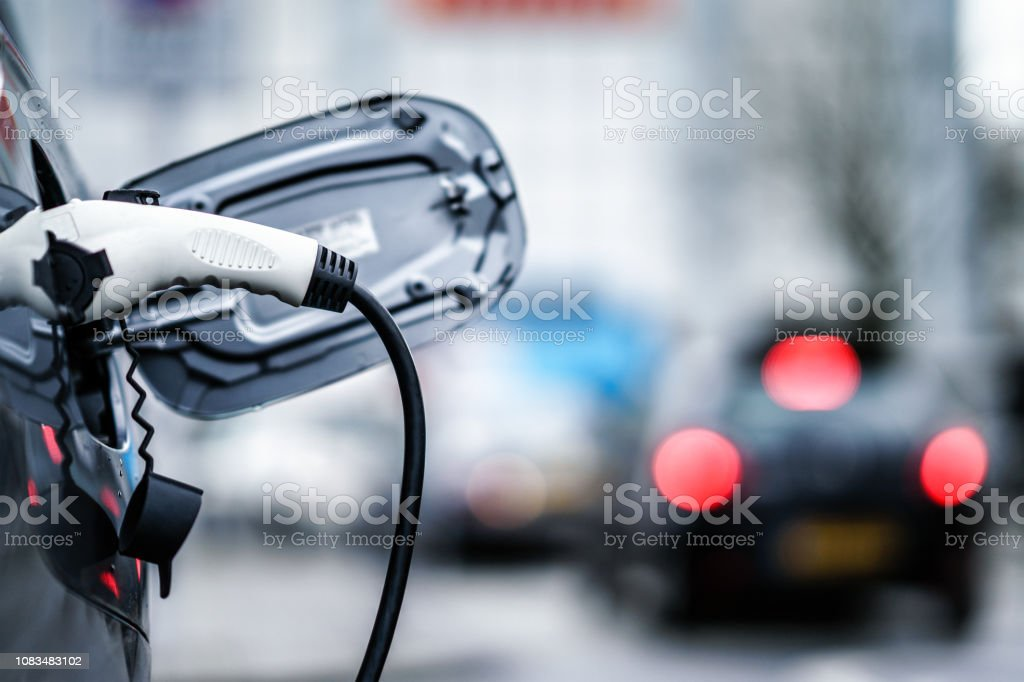 Electric Vehicle is changing in street. Electric Vehicle is changing in street. Alternative Fuel Vehicle Stock Photo