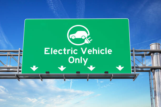 Electric vehicle only green traffic road sign with symbol of electric car on sky background. Ecology and environmental concept background. stock photo