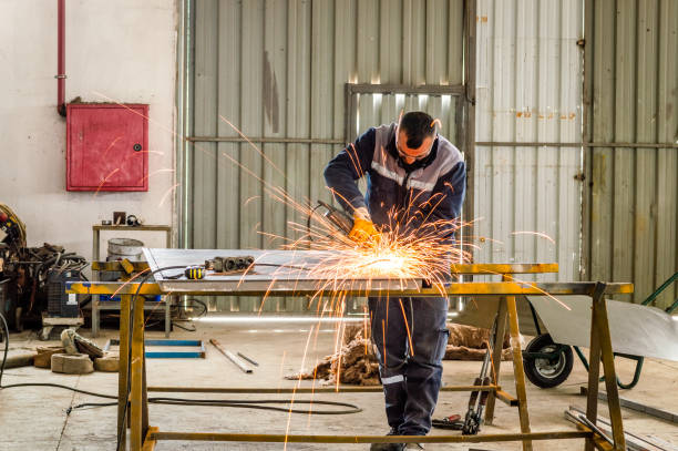Electric wheel grinding on steel structure in factory stock photo
