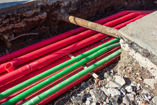 A large number of modern plastic cable protection pipes for electricity cabling (in the red pipe ducts) and fibre optic (green), during an installation in a trench dug in the street.