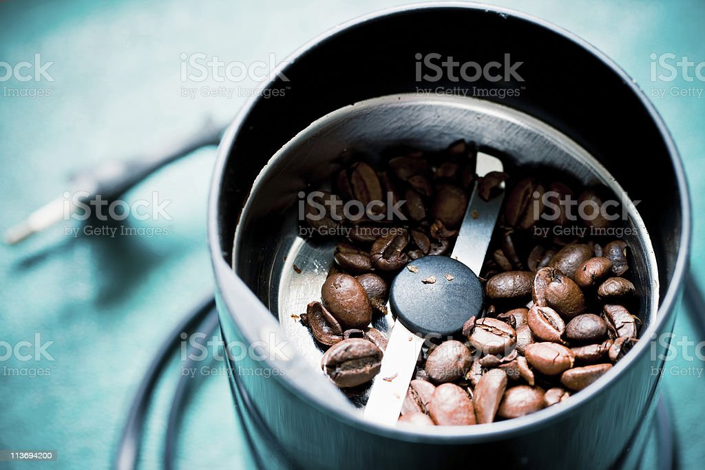 Electrical coffee-mill machine with roasted coffee beans stock photo