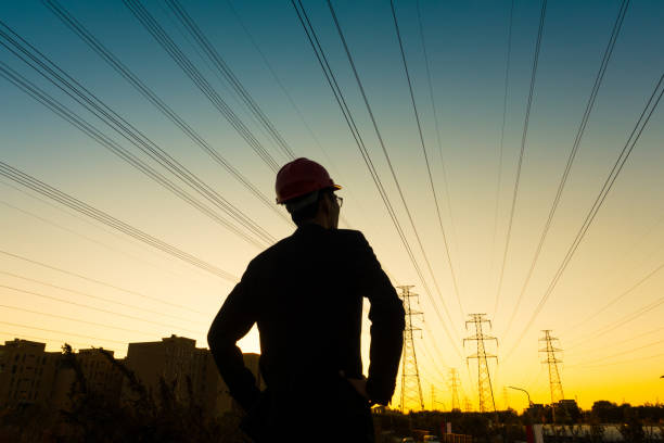Electrical engineer at sunset,Back Lit Electrical engineer at sunset,Back Lit power occupation stock pictures, royalty-free photos & images
