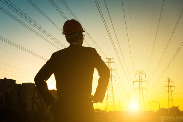 electrical engineer at sunset,back lit - rete elettrica foto e immagini stock