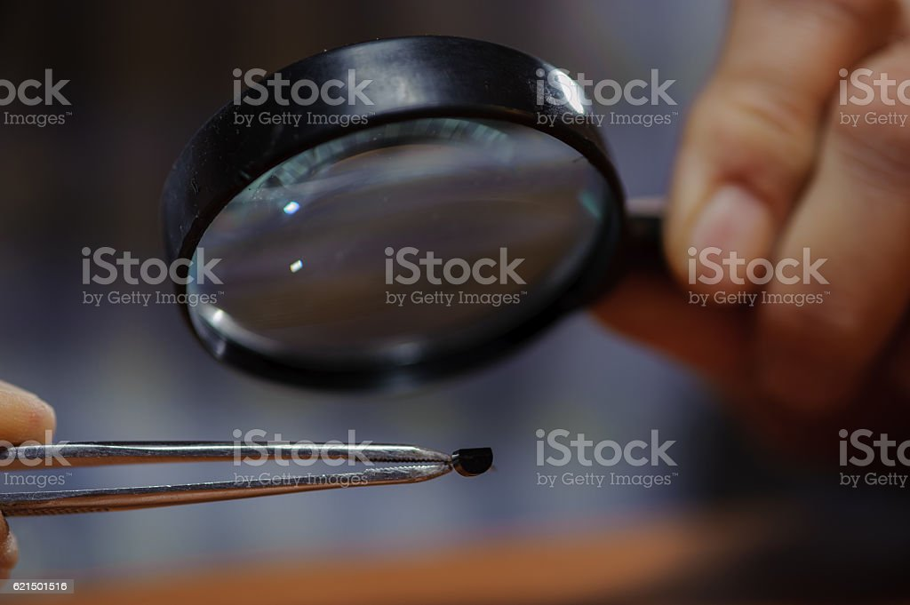 Electrical engineer checking diode with magnifier foto stock royalty-free
