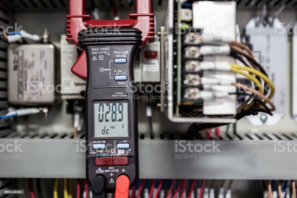 Electrical Engineer is check electrical equipment with a multi-meter - Zbiór zdjęć royalty-free (Bezpieczeństwo)