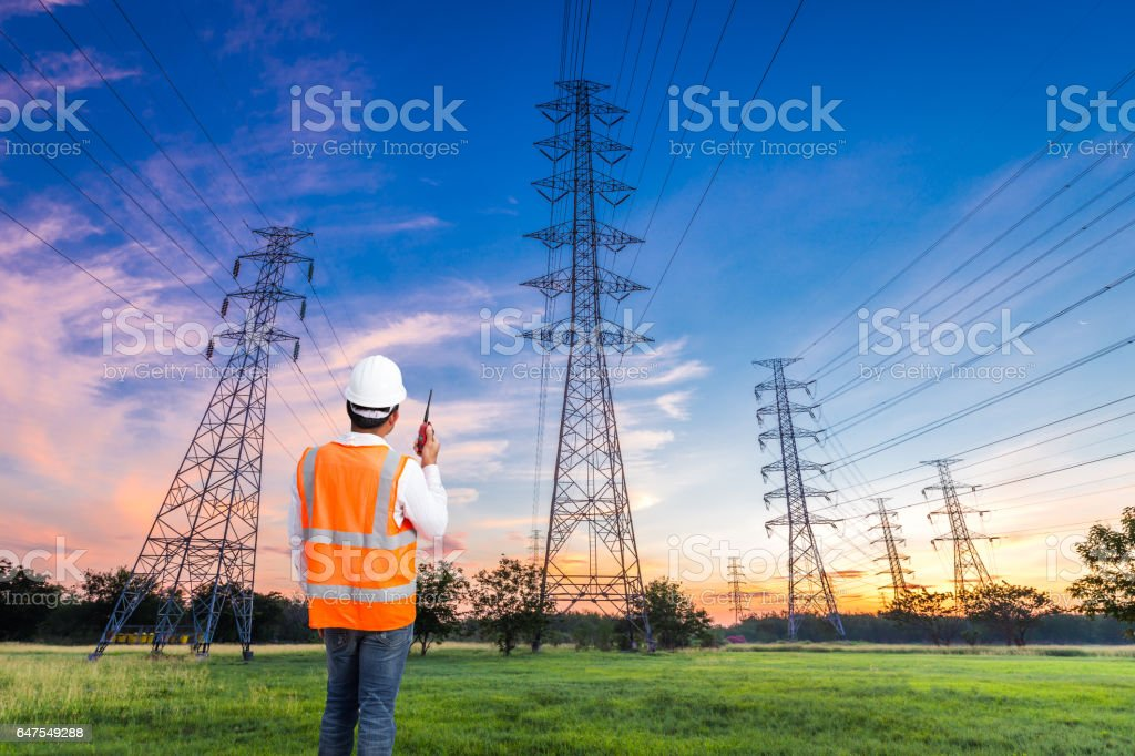 Electrical engineer with high voltage electricity pylon at sunrise background stock photo