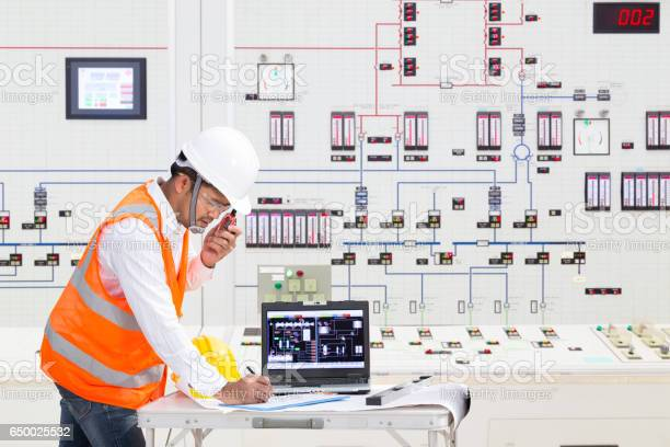 Electrical Engineer Working At Control Room Of Thermal Power Plant Stock Photo - Download Image Now