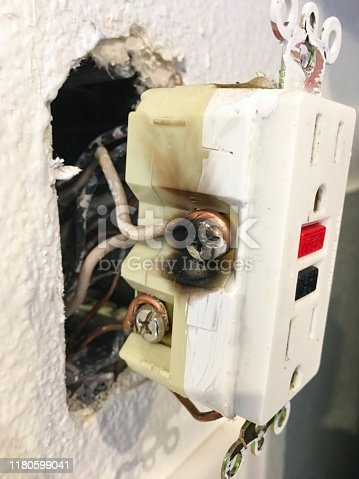 A GFCI outlet with black area from overheating. Receptacle shows the white neutral wire side. Mobilestock. Taken on mobile device.