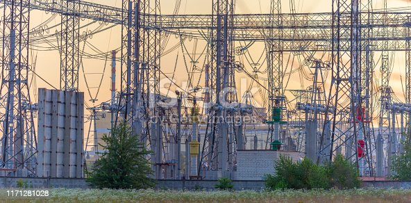 istock Electrical high voltage compensation station in front of 2 RBMK type nuclear reactors at sunset. 1171281028