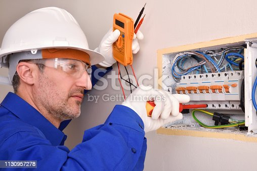 Electrical installer with protective elements working in an electrical panel of a house.