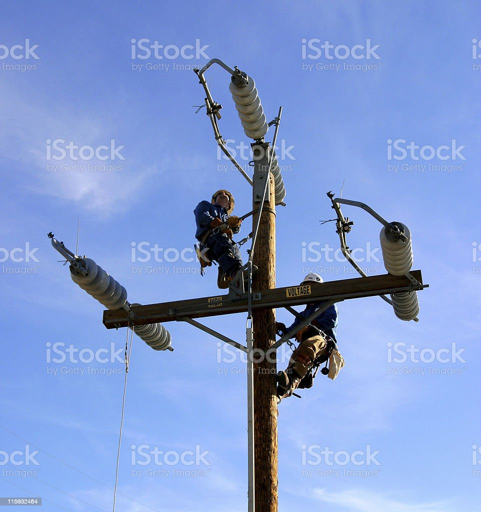Electrical linemen on electric power pole royalty-free stock photo