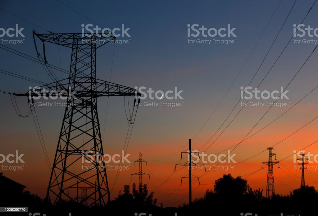Electrical lines under a night sky with moon. power electric line and...