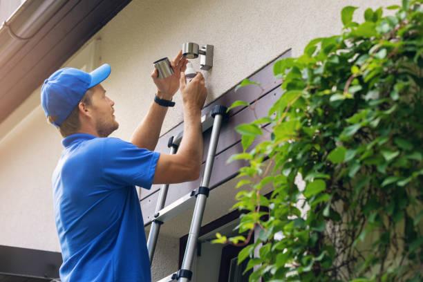 elektrische wartung - elektriker ändern glühbirne im haus außen wandleuchte - glühbirne auswechseln stock-fotos und bilder
