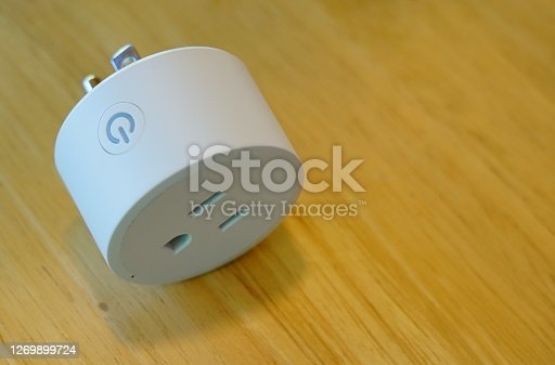 Smart Power Socket of White color on Smart Wi-Fi plug  switch with support for control via mobile on floor.