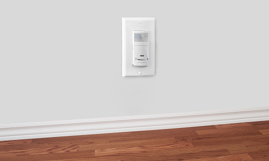 Horizontal photo of female hand inserting power cord receptacle into electric wall outlet