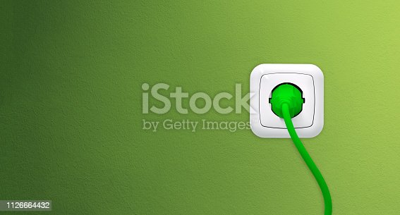 Electrical outlet with plug on green wall