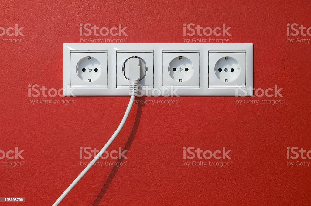 Electrical outlets, cable and electric plug on red textured wall royalty-free stock photo