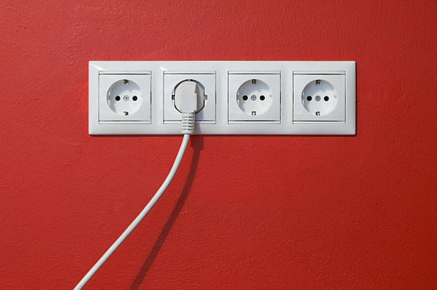 Electrical outlets, cable and electric plug on red textured wall stock photo