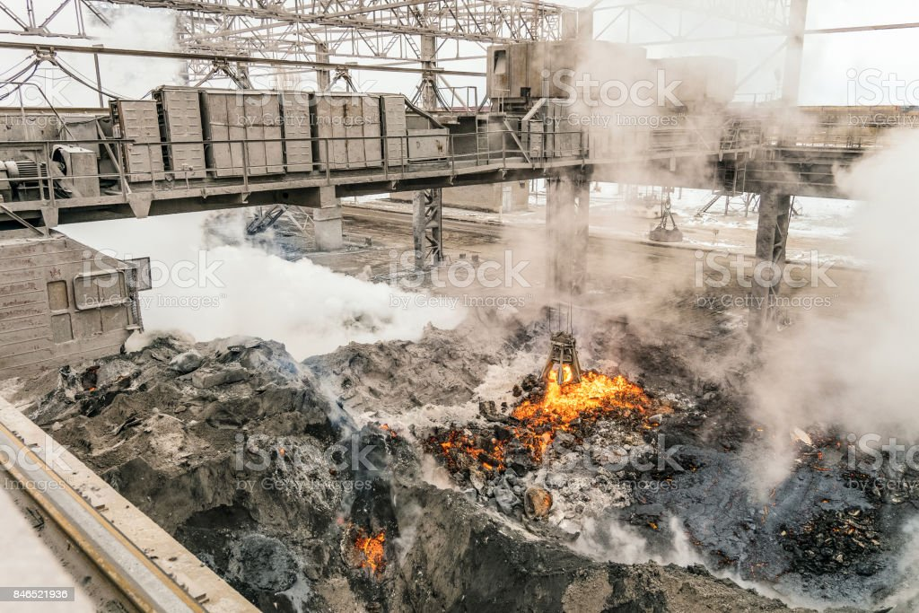 Electrical overhead crane with mechanical multivalve clamshell grapple over evaporation of molten liquid red-hot iron and slag in slag dump. Metallurgical heavy industry. stock photo