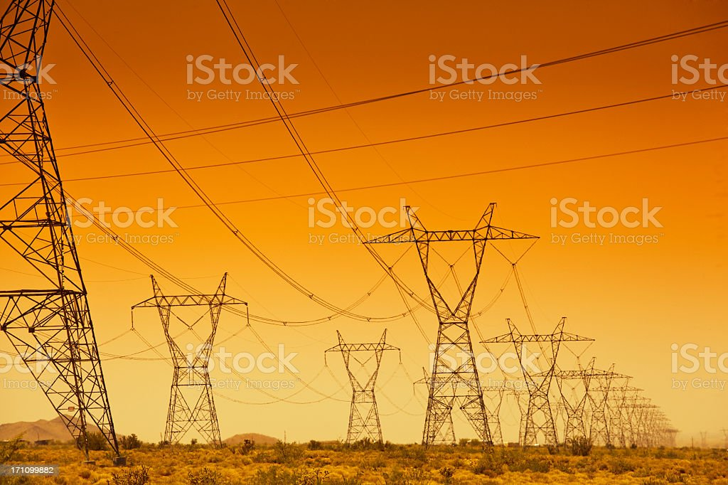 Electrical Power Line Grid Across the Landscape at Sunset stock photo