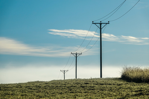 Electrical power line over misty field.