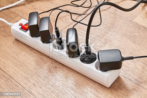 Electrical power strip overloaded with multiple electrical cords plugged in. Many plugs plugged into electric power bar