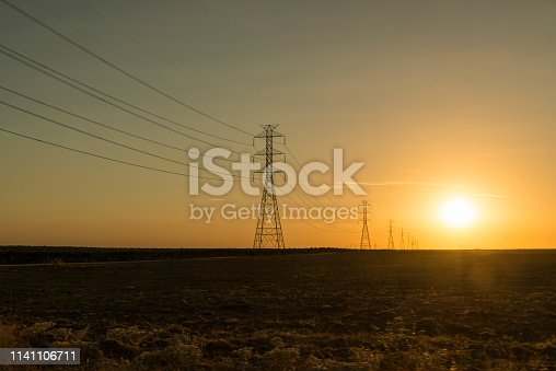 Electric power transmission lines on a field with sunset on the background