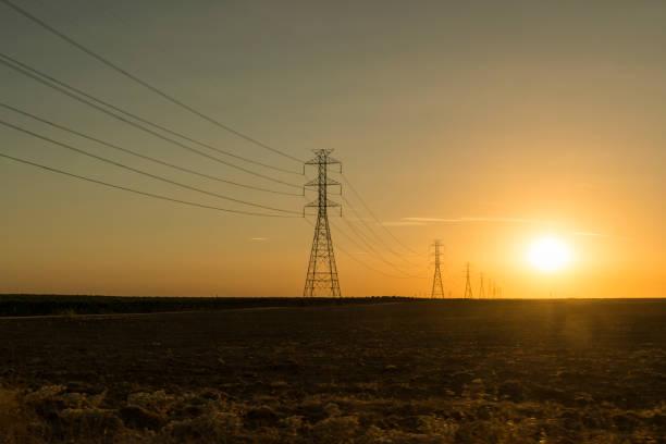 stromübertragungsleitungen und pylonen bei sonnenuntergang - stromkabel stock-fotos und bilder