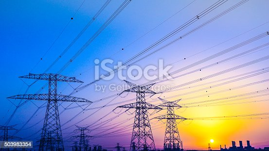 Electrical Pylons against vibrant twilight colors and a gorgeous sunset over Dubai Horizon.