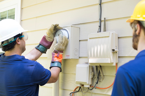 Latin and Caucasian workmen changing out meter on a residential home.  The man wearing white hat wears safety goggles.