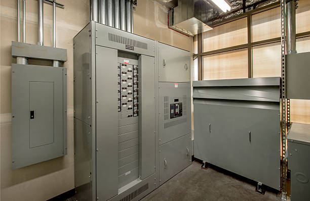 Electrical Room for an Office Building Transformer and control panel in the electrical room of a large office building. electricity transformer stock pictures, royalty-free photos & images