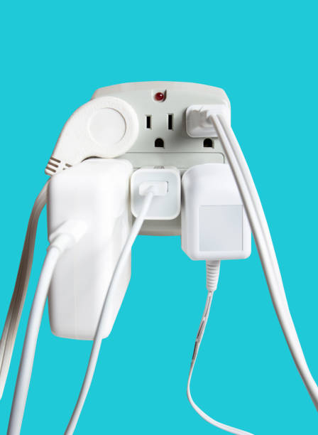 Electrical socket overloaded on wall. Electric wires plugged into socket stock photo