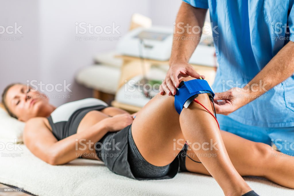 Electrical stimulation in physical therapy. Therapist positioning electrodes onto a patient's knee stock photo