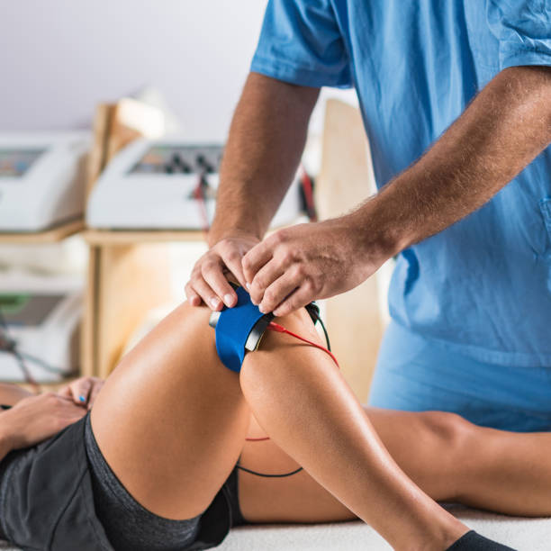 Electrical stimulation in physical therapy. Therapist positioning electrodes on a patient's knee stock photo