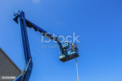 istock Electrical technician repairing street light by boom lift 922594896