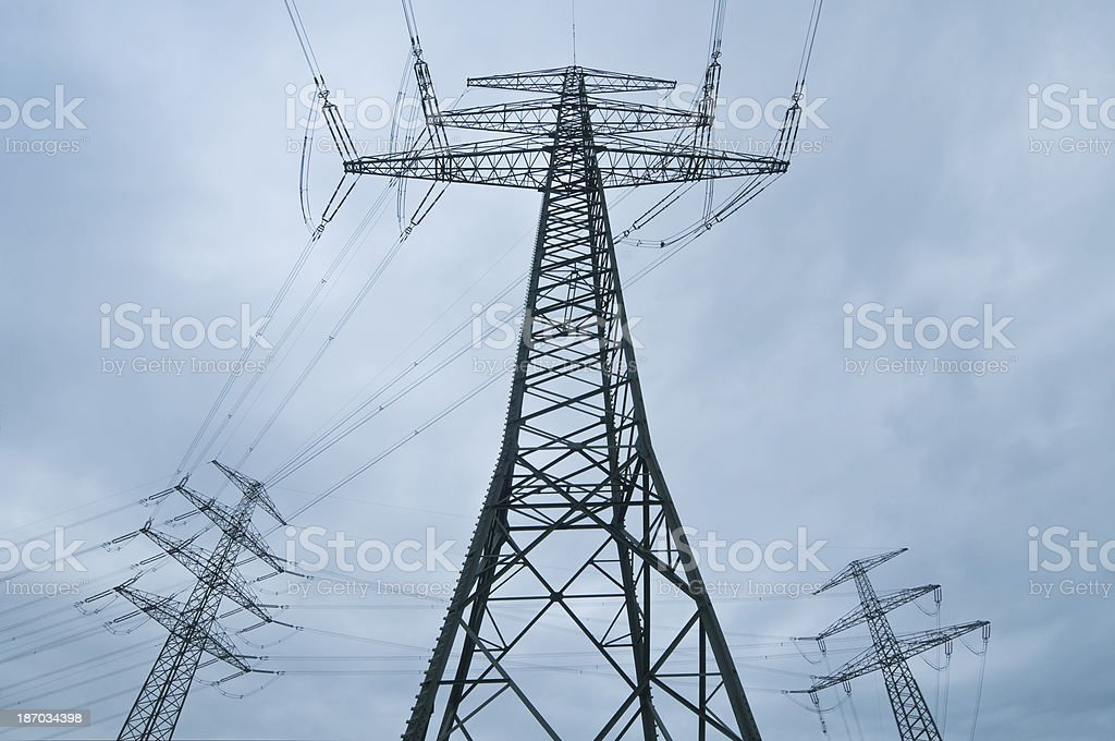 Electrical towers and cloudy sky stock photo